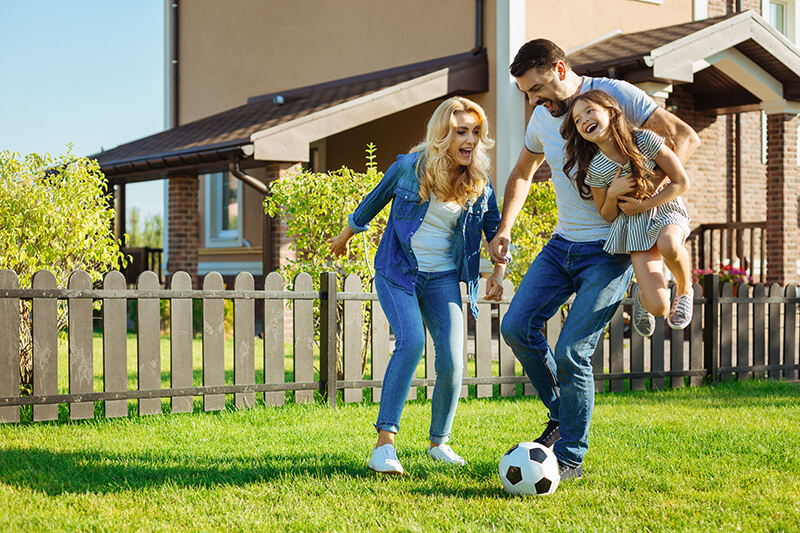 a family playing soccer on the lawn