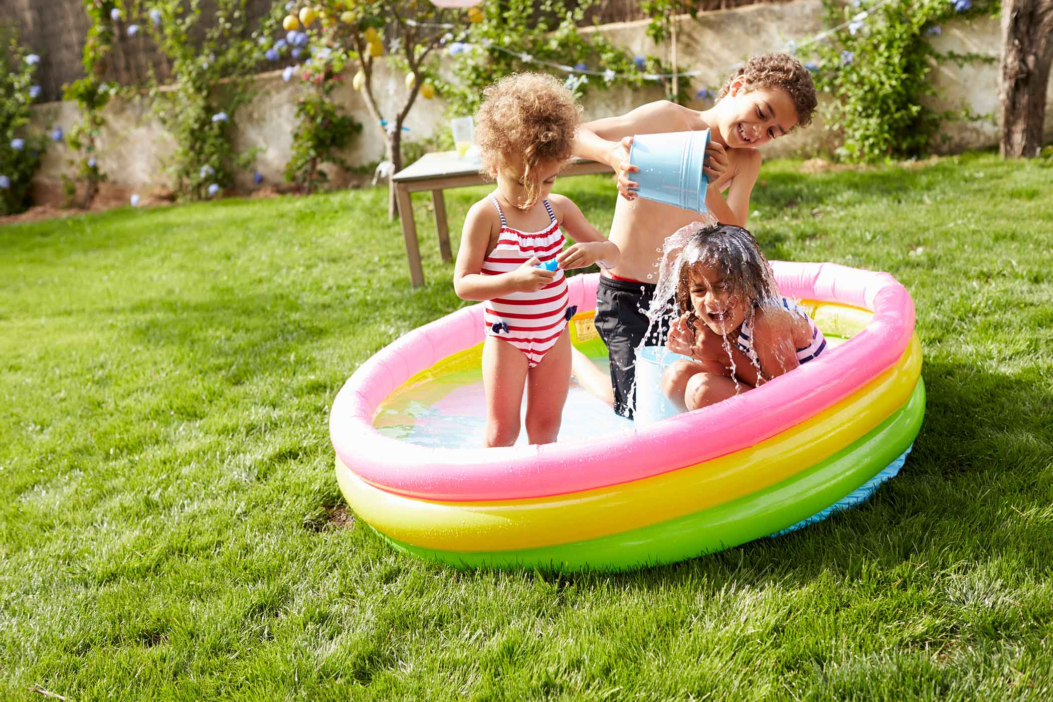 three kids playing in an inflatable pool