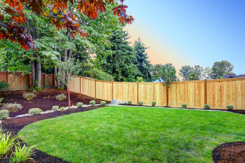landscaping with mulch up against a wooden privacy fence
